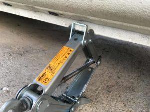 タイヤ交換でジャッキを車にかけているところの写真